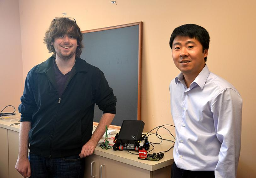 Senior Math major Travis Pitchford (left) and Computer Science professor Dr. Zaixin Lu (right) stand next to their wireless power transfer apparatus.