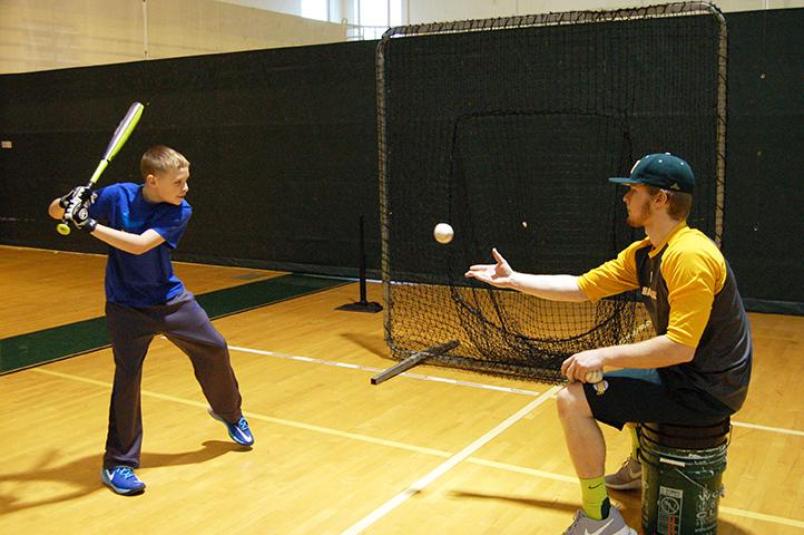 Sophomore Athletic Training major and first baseman Matt Staback tosses the ball to 6th grader AJ Keller at the