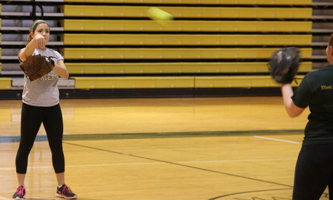 Mackie Goodwin practices in the gym with the softball team.