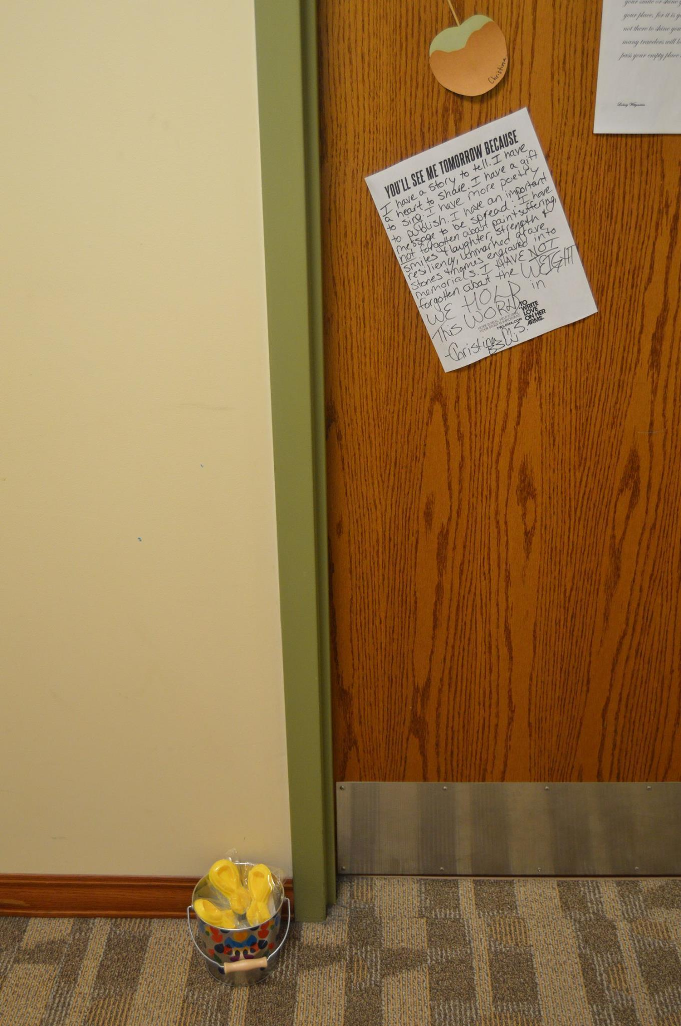Outside of Christina's dorm door a can of lollipops and awareness signs on her door.
