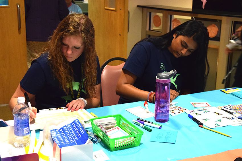 Kidstuff student volunteers Claudia Shandra and Deanna Ramdeo work outside of the Latour Room.