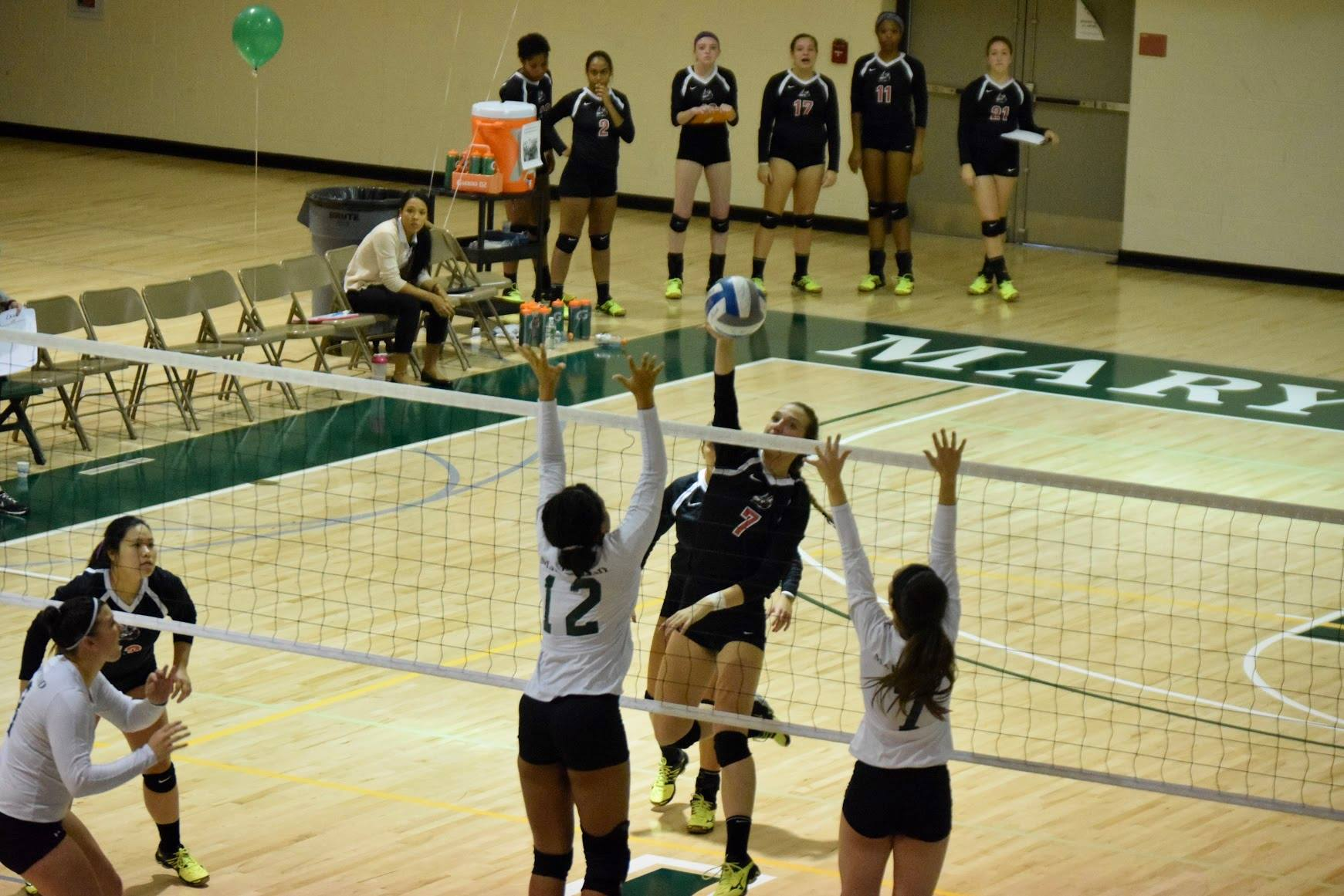 Freshman Mikayla Attwood and junior Danielle DeIulio attempt to block a spike from the Valiant's Kerry Mackey
