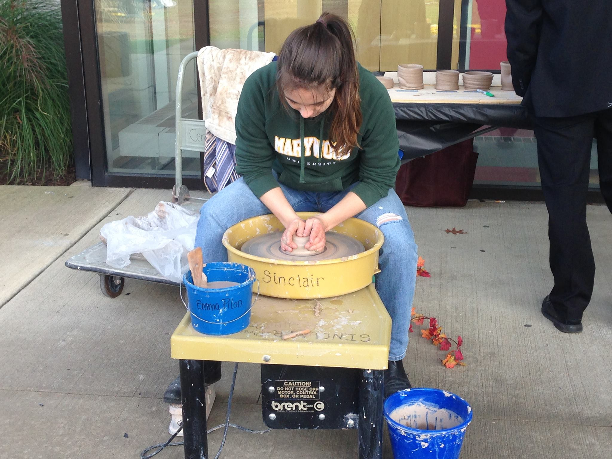 Senior ceramics/art administration major Emma Pilon does a pottery demonstration for students.