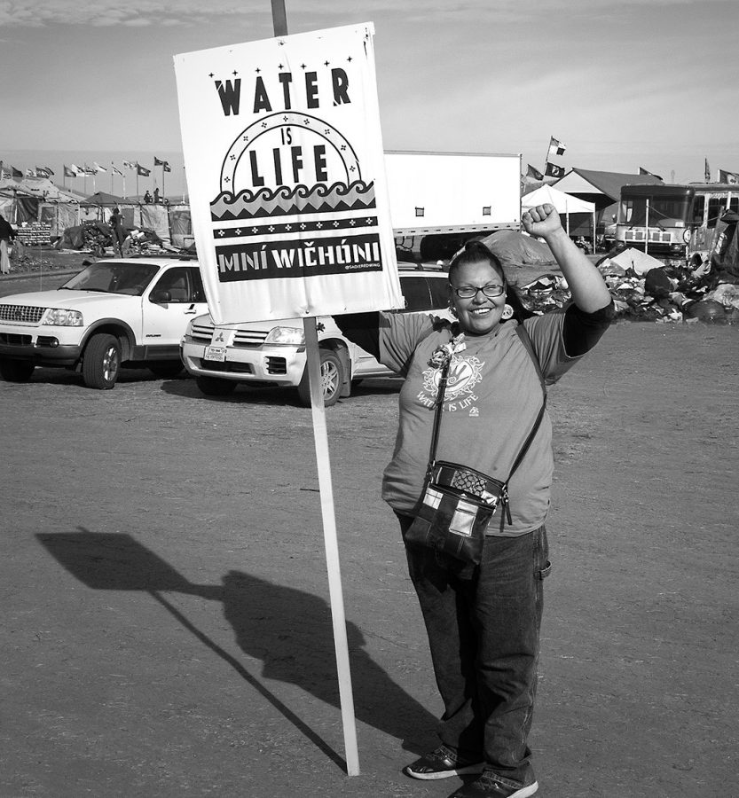 A+protester+holds+a+sign+reading+%22Water+Is+Life%22+in+English+and+Lakota.+Photo+courtesy+of+Dr.+Michael+Mirabito+%28Copyright+2016%29