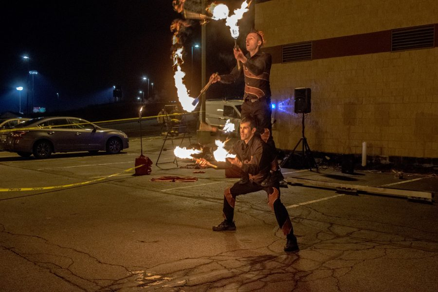 Tim Ellis juggles fire batons while balancing fellow performer Michael Mucciolo on his legs.