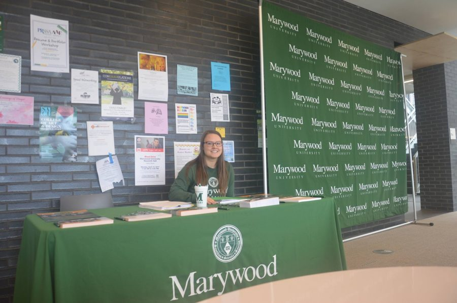 Melissa Przewlocki, graduate assistant for The Office of University Advancement and graduate student in higher education and administration, assists with the Giving Day table in the Learning Commons.
