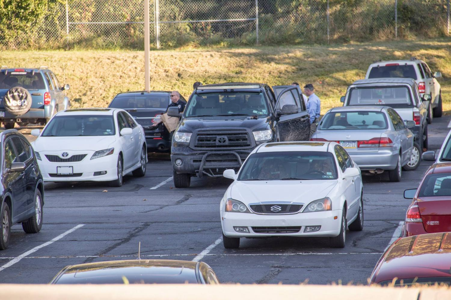 The suspect's vehicle, a black Toyota pickup, was searched in the upper pit parking lot behind Loughran Hall.