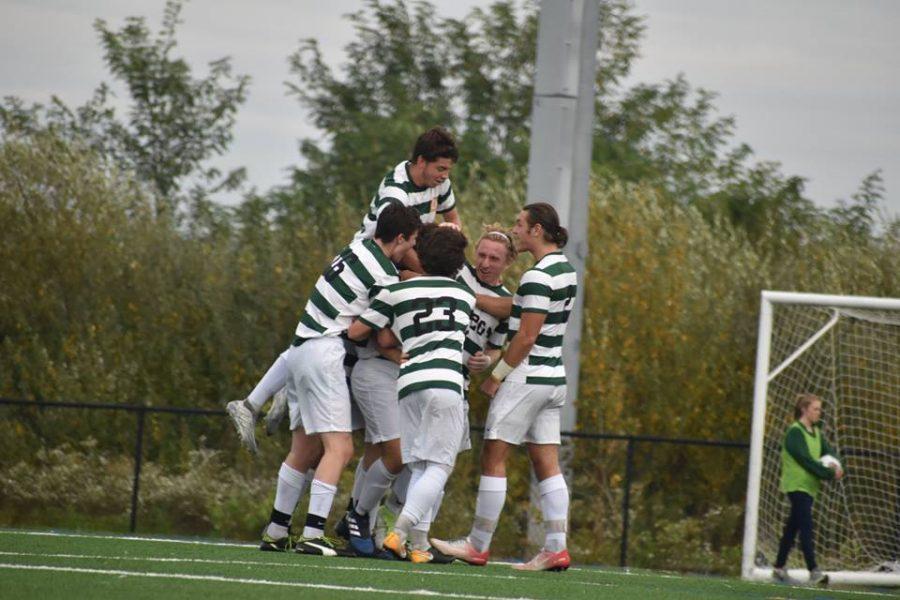 The men's soccer team celebrates after scoring a goal against the Highlanders.