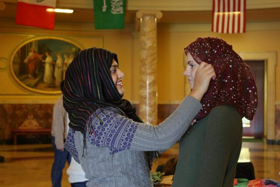 Organizer+Salma+Ahmed%2C+left%2C+shows+a+student+how+to+put+on+a+hijab.