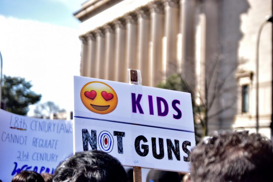 Attendees at the March for Our Lives rally hold signs.