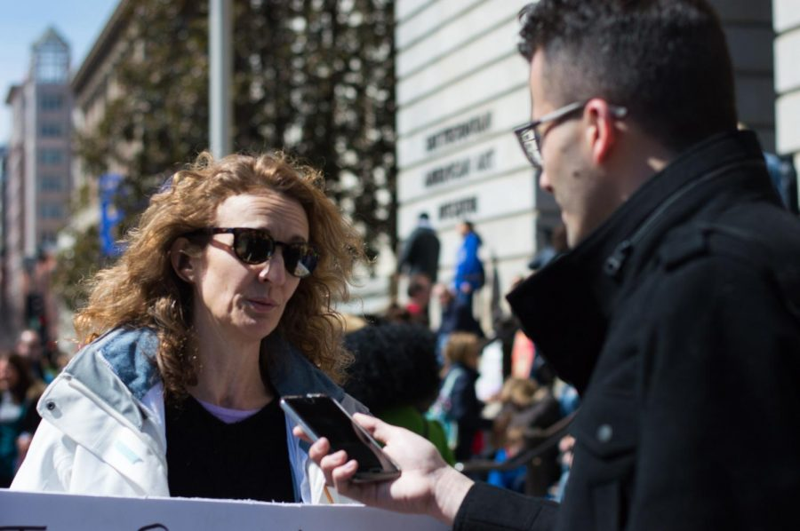 Sports Editor John Ferraro asks Karen Siatras from Maine questions about why she marched in Washington D.C. Photo credit: Manfid Duran